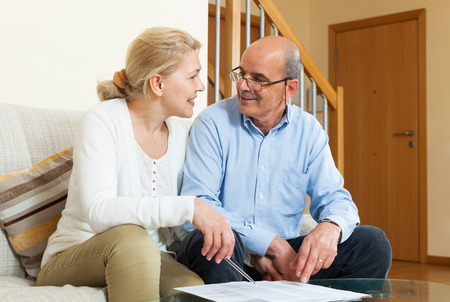 parsimony: Happy elderly couple with financial documents on sofa in home interior Stock Photo