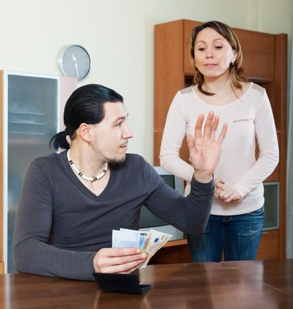 cupidity: Husband counting money, woman watching him in home