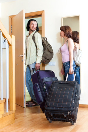 Young positive couple with luggage near door going on holiday photo