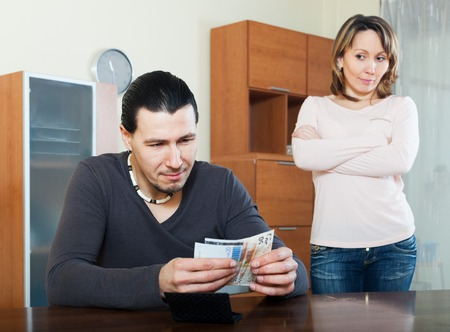 covetous: Man counting money, wife watching him in home
