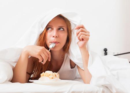 Hübsches Mädchen essen Keks in ihrem Bett Standard-Bild - 28134361