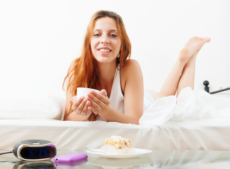 Smiling girl with mug of cafe in her bed at home photo