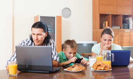 Happy couple with teenager child using devices during breakfast in home interior photo