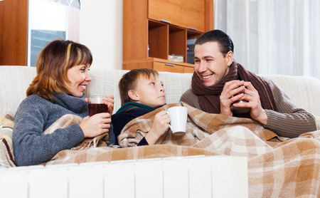 Happy family of three with cups of tea warming near warm radiator in home Фото со стока