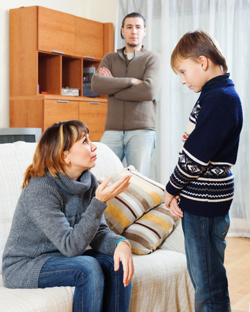 Mother and father scolding teenager  at living room photo