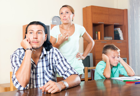 Family of three with teenager boy having quarrel at home photo