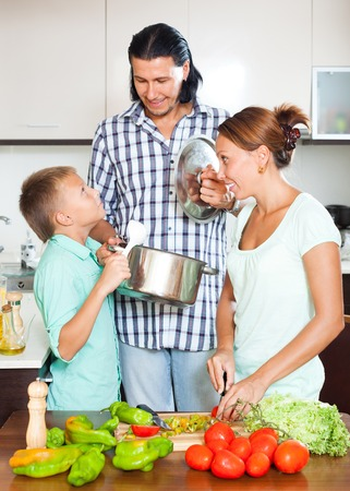 Happy family cooking veggy lunch in home kitchen photo