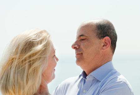 Happy mature couple together with sea beach in background. Focus on man photo