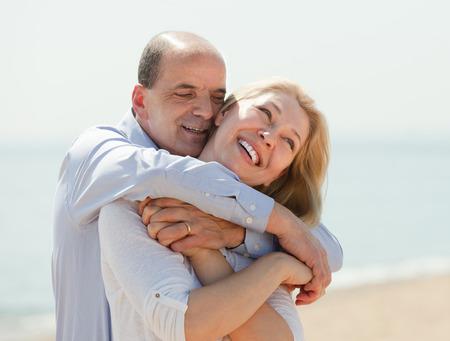 spouses: Happy international family in years having honeymoon at sea shore in warm season