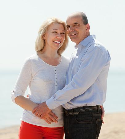 happy loving mature couple against sea in background photo