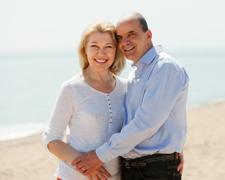 mature couple against sea in background photo