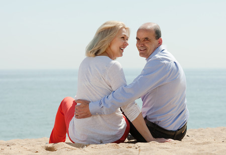 Rear view of loving mature couple at  beach photo