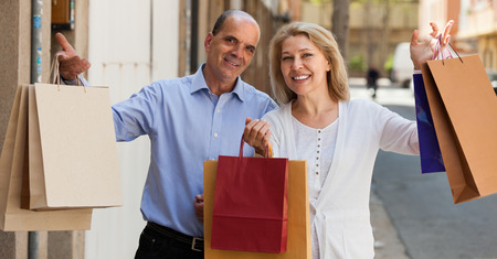 Smiling aged couple staying at street with purchases in hands photo