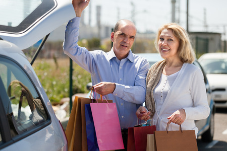 Smiling elderly couple putting bags with purchases in trunk  photo