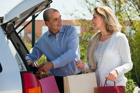 novelties: Happy mature husband and wife with shopping bags near a car Stock Photo