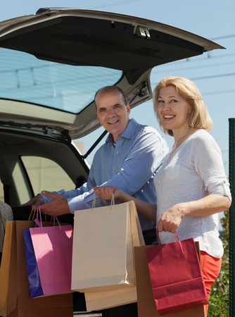 Senior spouses with bags near car at shopping center parking lot photo
