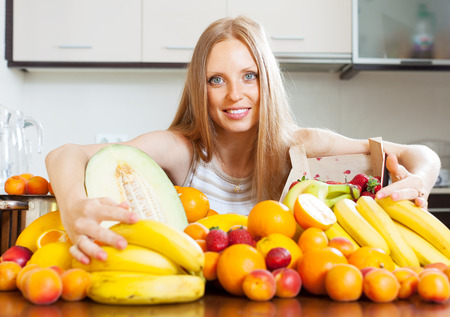 young blonde housewife with fresh fruits at  kitchen  photo