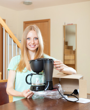 coffeemaker: Cute blond unpacking and reading manual for new coffeemaker  Stock Photo
