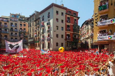 begining: PAMPLONA, SPAGNA - 6 luglio: Inizio del Festival di San Fermin a 6 luglio 2013 a Pamplona, ??in Spagna. Felice folla di persone solleva scialle rosso in Ayuntamiento