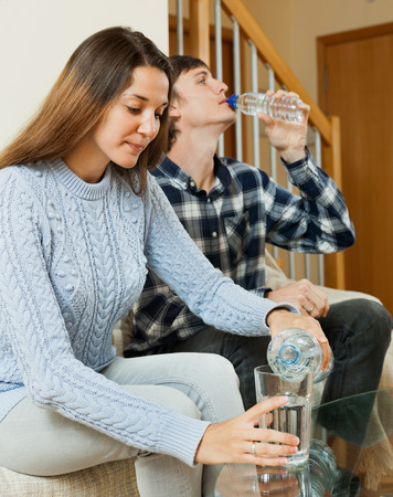 Young man and woman sitting on the couch and drink fresh water photo