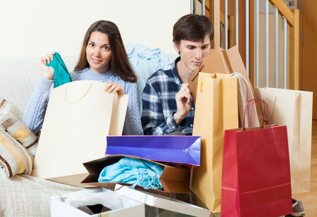 disgruntled: Woman showing purchases  to disgruntled boyfriend
