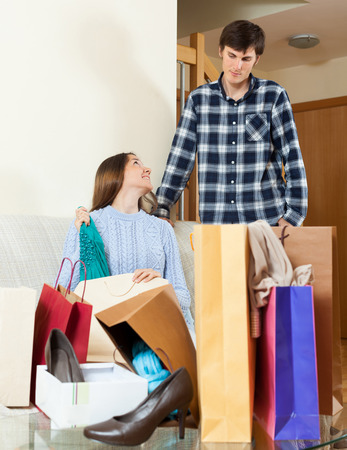 disgruntled: Smiling woman showing purchases  to disgruntled boyfriend Stock Photo
