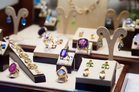 neckless: Gold jewelry with gems at showcase of jewelry shop