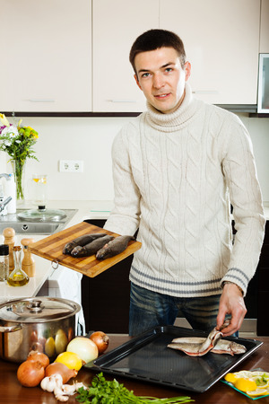 Handsome man putting  raw trout into roasting pan at kitchen table photo