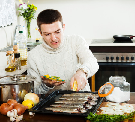 Handsome man cooking trout fish with lemon in baking shee photo