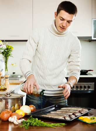 Handsome man pouring oil in raw fish on roasting pan at home kitchen  photo