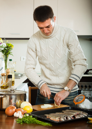 roasting pan: Handsome guy cooking raw fish with  onion in roasting pan at  kitchen