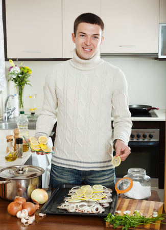 roasting pan: Handsome guy cooking  fish with lemon in roasting pan at home kitchen