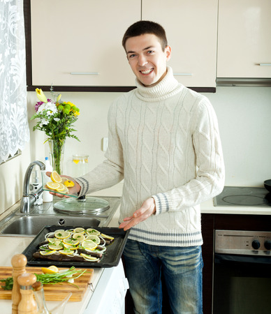 Smiling man putting pieces lemon in fish at home kitchen photo