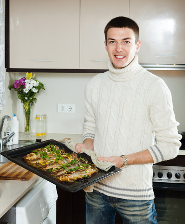 Smiling guy with cooked fish on  frying pan at home  kitchen photo