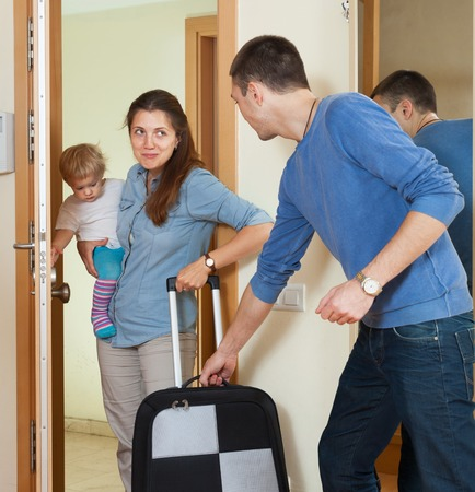 Happy family of three with child with luggage leaving the home photo