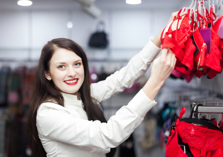 Young female buyer choosing bra at clothing store photo