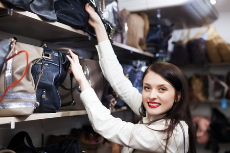 Ordinary fermale customer choosing leather bag at store  photo