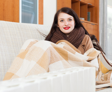 Portrait of  woman warming near electric heater at  home