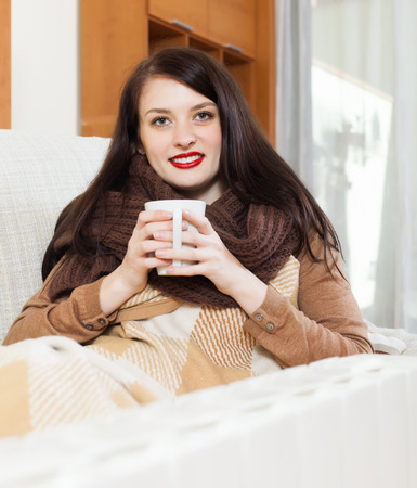 Happy girl with cup near calorifer  in home Stock Photo