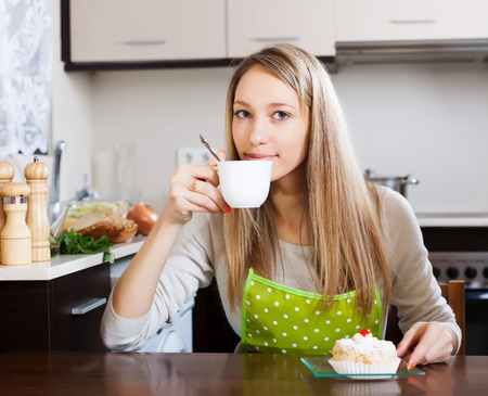 Smiling woman drinking tea with cake at table in home photo