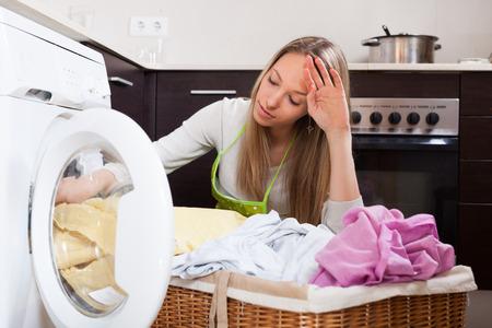 lavando ropa: mujer cansada que hace el lavadero con lavadora