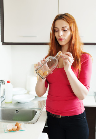 tojáshéj: Girl washing glass bottle with egg shell in the kitchen