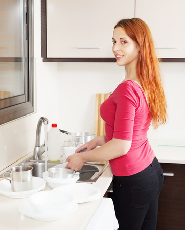 Happy housewife in red washing kitchenware in home kitchen photo