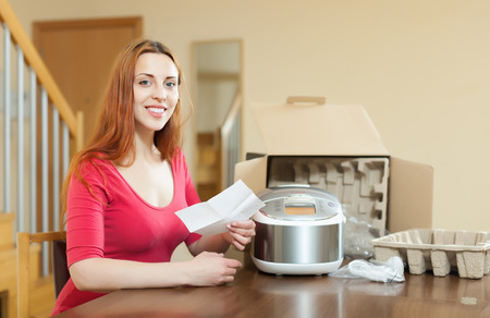 slow cooker: Happy woman  reading  warranty card for new slow cooker at home