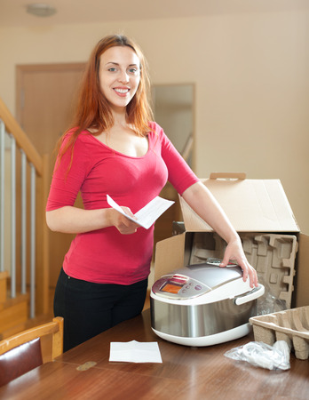Happy young  housewife unpacking new multicooker in living room  photo
