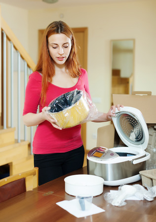 young woman looking new multicooker in home interior photo