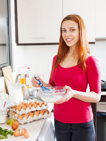 Woman beating eggs and milk in  bowl at  kitchen Stock Photo
