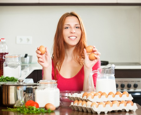 Smiling housewife in red making dough with eggs in domestic kitchen photo