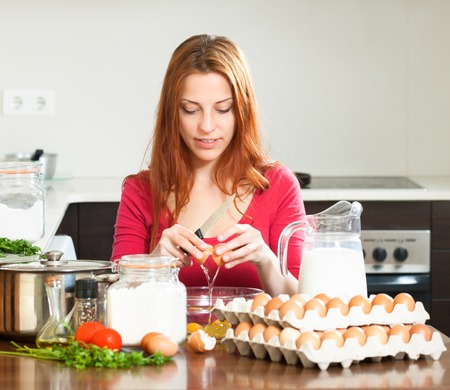 girl in red cooking omelet with eggs in home kitchen photo
