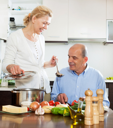 smiling mature couple cooking together in  home kitchen photo